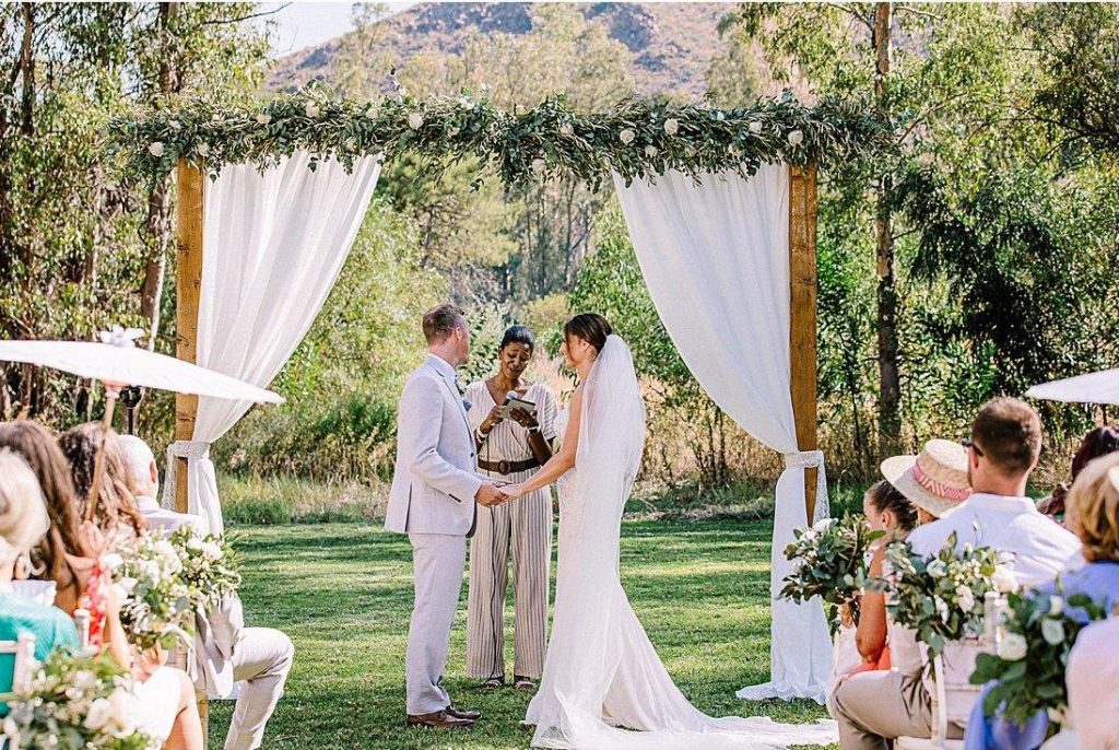 Man and woman getting married in garden ceremony